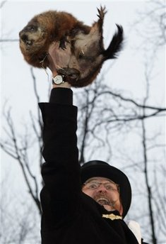 Ben Hughes, handler of the weather-predicting groundhog Punxsutawney Phil, holds Phil in the air after removing him from his stump at Gobbler's Knob on Groundhog Day, Monday, Feb. 2, 2009, in Punxsutawney, Pa. The Groundhog Club said Phil saw his shadow and predicted six more weeks of winter. (AP Photo/Carolyn Kaster)